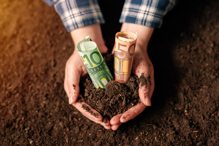 soldi-agricoltura-banconote-euro-terreno-mani-by-bits-and-splits-adobe-stock-749x500.jpeg
